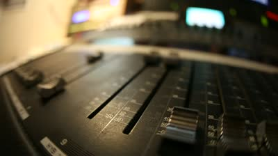 stock-footage-sound-director-working-on-audio-mixer-in-professional-studio-sharp-near-of-hand-a-little-dof